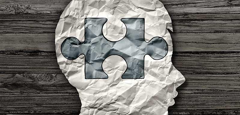 Silhouette en papier froissé d'une tête d'enfant avec une pièce de puzzle dessinée